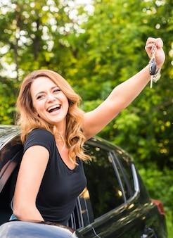그녀의 첫 번째 새 차의 키를 들고 젊은 쾌활 한 즐거운 웃는 화려한 여자. 고객 만족.
