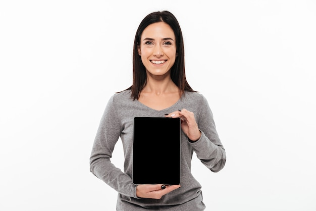 Young cheerful lady showing display of tablet computer.