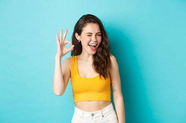 Young cheerful lady in summer clothes winking and saying yes, alright gesture, making ok sign in approval, standing against blue background.