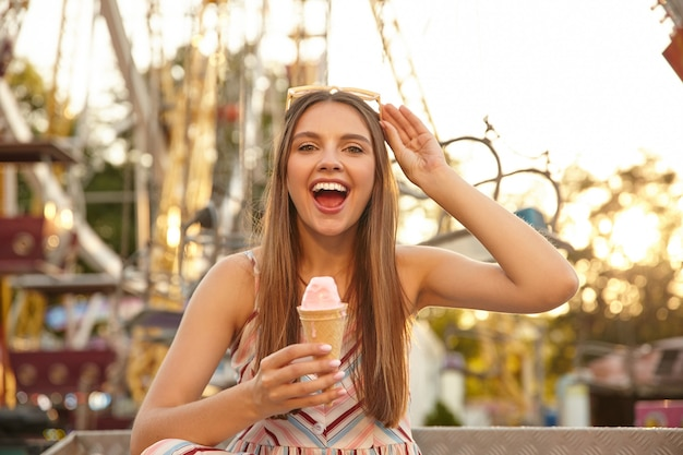 Young cheerful long haired pretty lady with sunglasses on her head looking with broad smile, eating ice cream cone while walking through park of attractions, wearing summer clothes