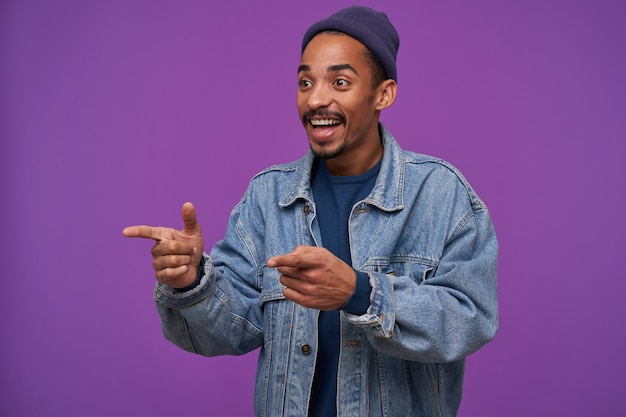 Young cheerful lovely dark skinned brunette man with beard pointing aside with raised forefingers and smiling widely while standing over purple wall