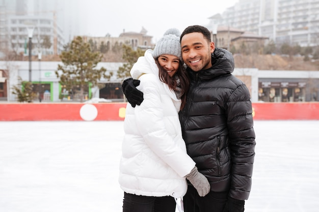 Young cheerful loving couple skating at ice rink outdoors.