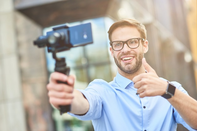 Young cheerful male blogger wearing blue shirt and eyeglasses holding a gimbal with smartphone