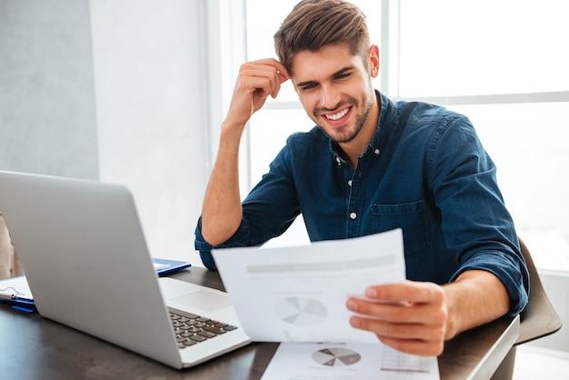 新聞を見ながらテーブルに座って財政を分析する若い陽気な男
