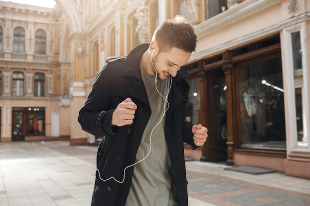 Giovane uomo allegro ballare ascoltando musica con le cuffie.