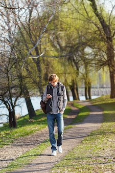 Young cheerful man in earphones strolls through the spring park and listens to music