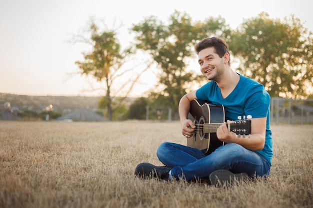 Young cheerful man playing guitar outside. positive vibe musician.