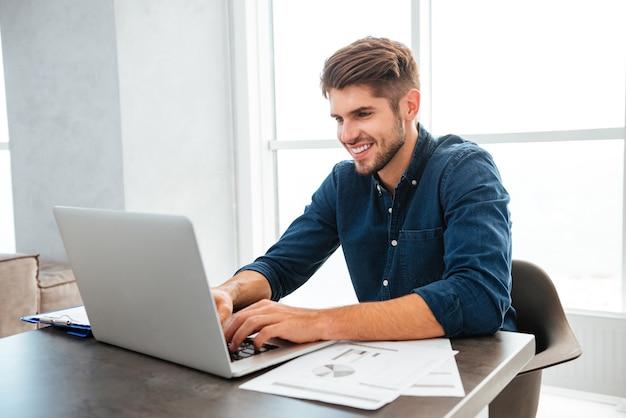 Молодой веселый человек usingop и сидит за столом с бумагами Premium Фотографии
