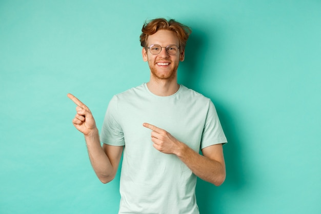 Young cheerful man with short red hair and glasses, pointing fingers left at copy space, smiling white teeth, showing advertisement, mint background