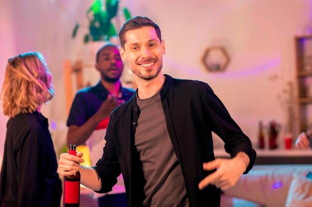 Молодой веселый человек с зубастой улыбкой держит бутылку пива во время танца перед камерой на фоне межкультурных друзей