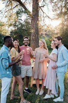 Молодые веселые мужчины и женщины разных национальностей веселятся с бокалами вина и слушают, как африканский парень произносит тост