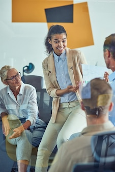 Young cheerful mixed race female office worker discussing sales report with colleagues while having
