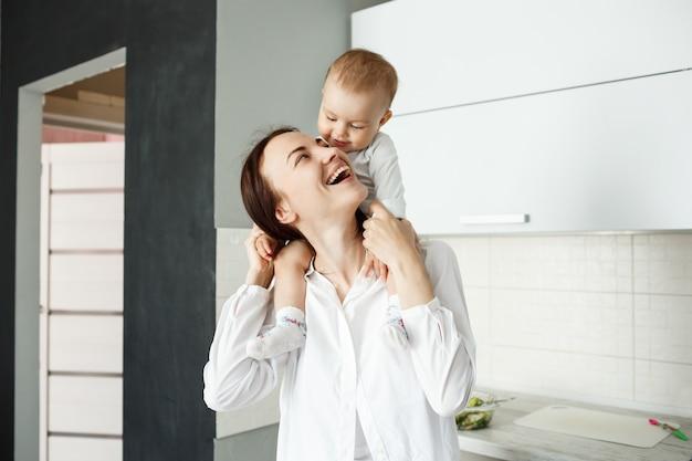 어깨에 아기를 들고 웃고 쾌활한 젊은 어머니