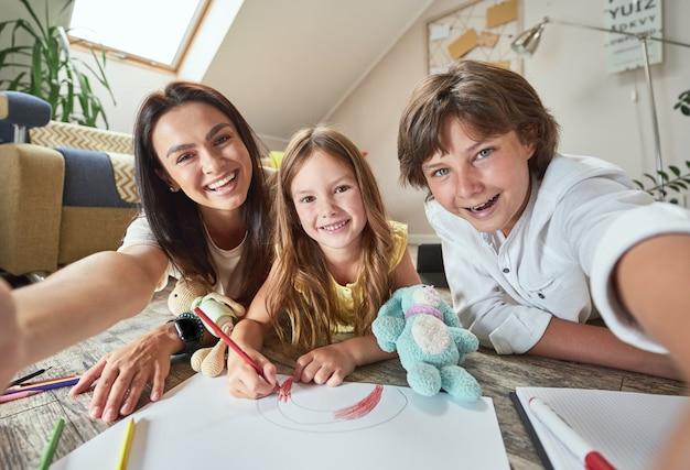 リビングルームの床に横たわって作っている2人の幸せな子供を持つ若い陽気な母親