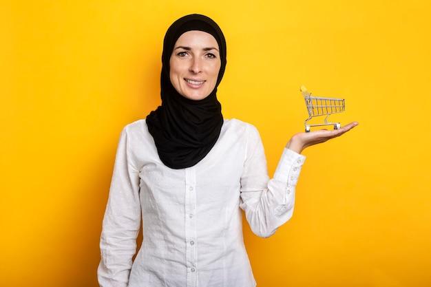 黄色のショッピングカートを保持しているヒジャーブの若い陽気なイスラム教徒の女性