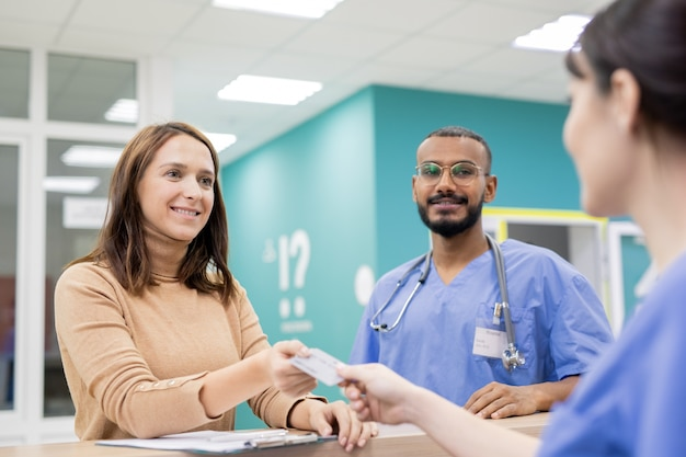 상담 및 치료 후 의료 서비스 비용을 지불하기 위해 병원 접수 원에게 신용 카드를주는 젊은 쾌활한 환자