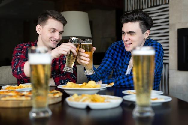 쾌활한 젊은이들은 미소를 짓고 술집에서 쉬는 동안 성공을 축하합니다.
