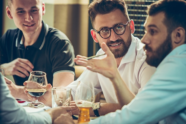 Young cheerful people smile and gesture while relaxing in pub.