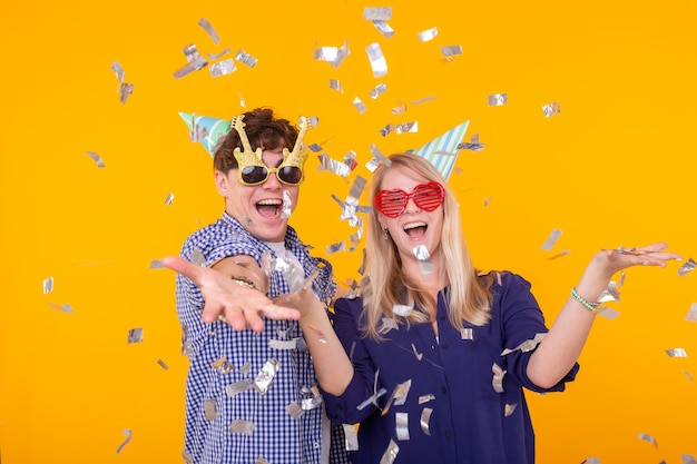 Young cheerful positive couple of funny glasses and a paper cap rejoice and shout on a yellow