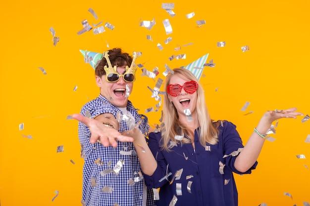 재미 있은 안경과 종이 모자의 젊은 쾌활한 긍정적 인 부부는 기뻐하고 노란색에 소리 질러