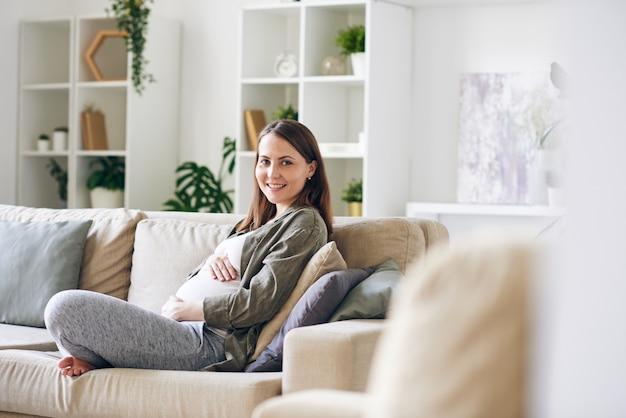 가정 환경에서 쿠션과 함께 소파에 쉬고있는 동안 이빨 미소와 함께 젊은 쾌활한 임신 한 여자