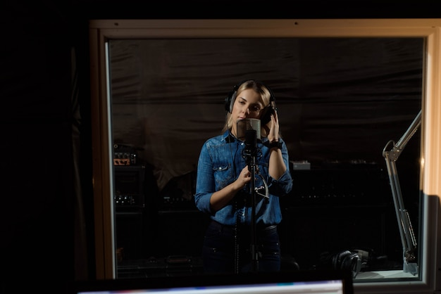 Young cheerful pretty smiling blonde woman recording a song
