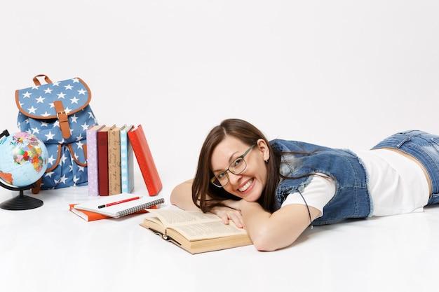 Giovane studentessa graziosa allegra in vestiti di denim e occhiali da lettura libro sdraiato vicino allo zaino del globo, libri scolastici isolati