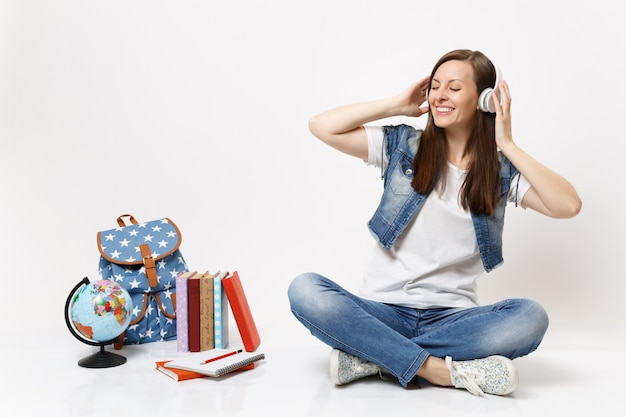 Young cheerful pretty woman student with closed eyes with headphones listening music sitting near globe backpack school book isolated