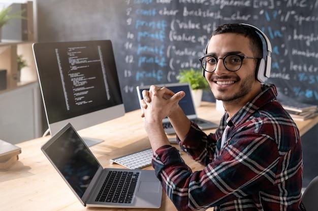 オフィスで新しいソフトウェアの作業中に笑顔であなたを見ているヘッドフォンを持つ若い陽気なプログラマー