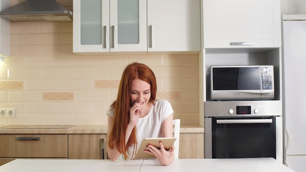 Young cheerful redhead girl sitting at the table in the kitchen reading the good news on her tablet