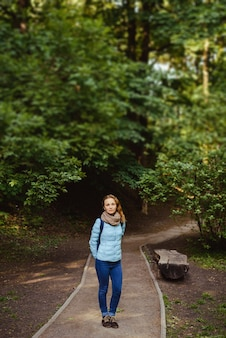 Young cheerful redhead woman in a blue jacket is happy outdoors in the park in the summer