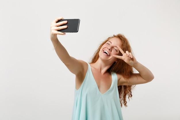 白い背景で隔離のポーズのカジュアルな明るい服を着た若い陽気な赤毛の女性の女の子。人々のライフスタイルの概念。コピースペースをモックアップします。携帯電話で自分撮りをして、勝利のサインを見せます。