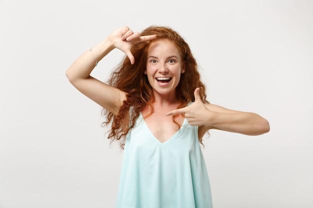 흰색 벽 배경, 스튜디오 초상화에 격리된 채 캐주얼한 가벼운 옷을 입은 젊고 쾌활한 빨간 머리 여자 소녀. 사람들이 라이프 스타일 개념입니다. 복사 공간을 비웃습니다. 손 사진 프레임 제스처 만들기.