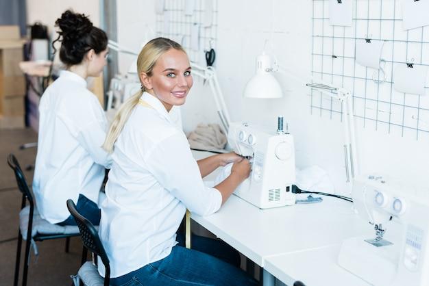 Молодая веселая швея в джинсах и белой рубашке смотрит на вас во время работы на электрической швейной машине на фабрике