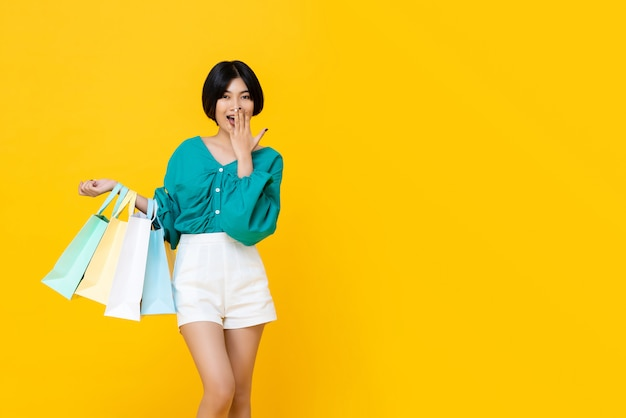 Young cheerful shopaholic asian girl with shopping bags