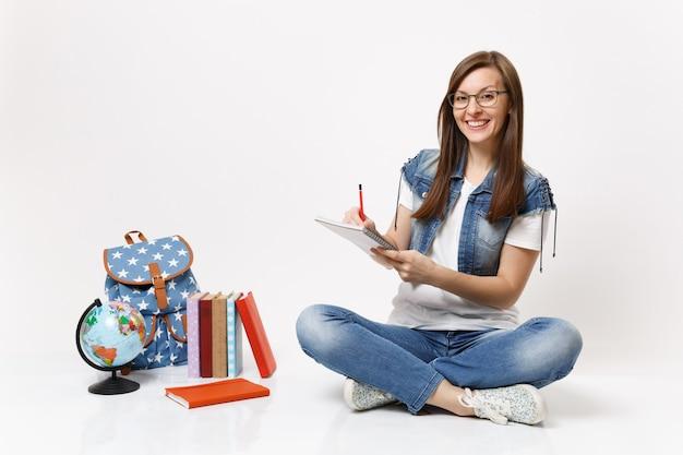 地球の近くに座っているノートブック、バックパック、白い壁に隔離された教科書にメモを書く眼鏡の若い陽気な笑顔の女性学生