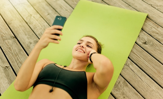 スポーツウェアの若い陽気なスポーツ女性は、屋外の木製テラスでマットの上に横たわっている間、音楽を聴き、彼の手でスマートフォンを保持します
