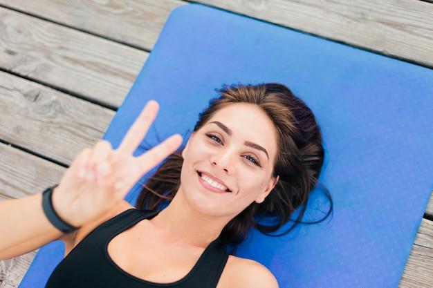 Молодая веселая спортивная женщина лежит на циновке и показывает символ v.