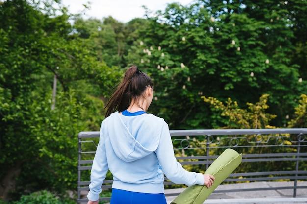 フィットネス敷物を保持している都市公園を歩いて若い陽気なスポーツ女性。
