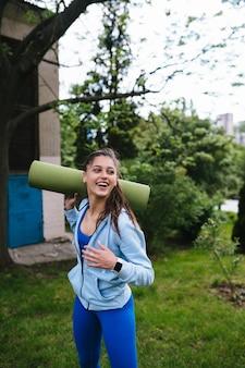Молодая веселая спортивная женщина, идущая в городском парке, держащем фитнес-коврик.