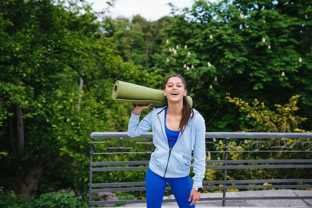 フィットネスラグを保持している都市公園を歩く若い陽気なスポーツ女性。