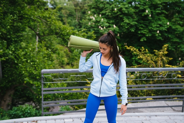 Young cheerful sports woman walking in urban park holding fitness rug.