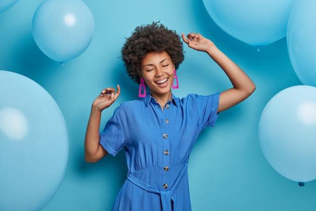 쾌활한 젊은 세련된 아프리카 계 미국인 여자가 제기 손으로 춤을 추고 축하 파티를 즐기고 유행 파란 드레스를 입고 움직입니다.