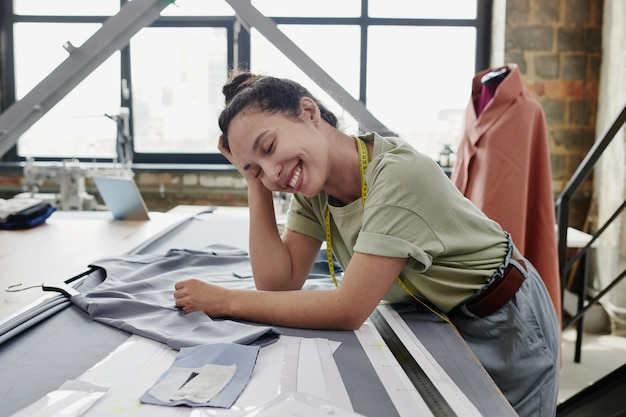 Young cheerful tailor or designer of clothes in casualwear leaning on table with unfinished dress, textile, paper patterns and ruler during work