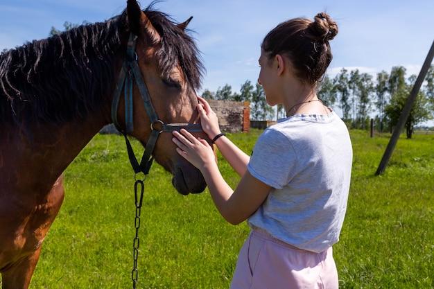 Молодая веселая девочка-подросток гладит нос коричневой лошади