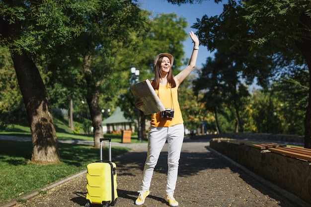 Young cheerful traveler tourist woman in hat with suitcase city map waving hand for greeting meet friend in city outdoor. girl traveling abroad to travel on weekend getaway. tourism journey lifestyle.