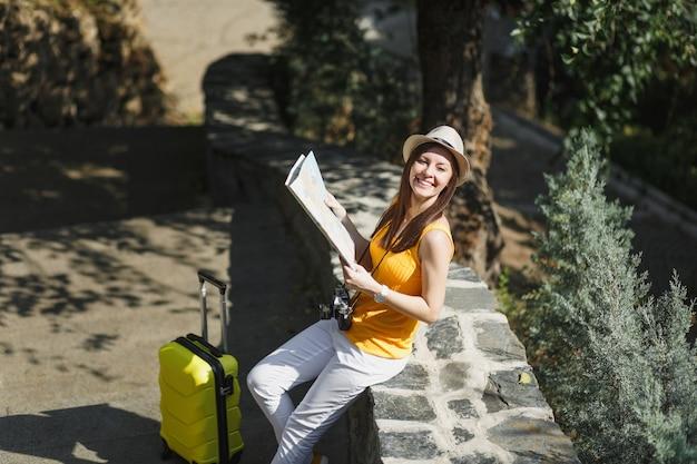 노란색 여름 평상복 모자를 쓴 젊고 쾌활한 여행자 관광 여성은 도시 야외에서 도시 지도를 들고 여행가방을 들고 있습니다. 주말 휴가를 여행하기 위해 해외로 여행하는 소녀. 관광 여행 라이프 스타일.