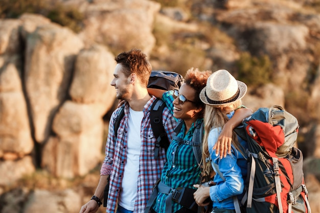 Young cheerful travelers with backpacks smiling, embracing, walking in canyon