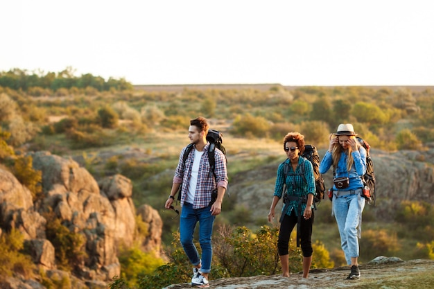 Young cheerful travelers with backpacks smiling, walking in canyon