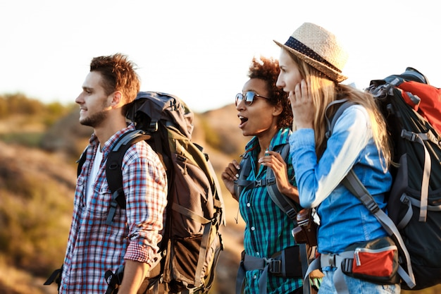 Young cheerful travelers with backpacks surprised, smiling, walking in canyon